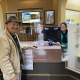 Customer Service Officer Alisha Davies assisting Mr Ken Lean, with perspex and signage in place for everyone's safety.